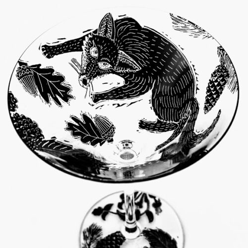 Martini glass with a woodcut style drawing of a Fox in a british woodland