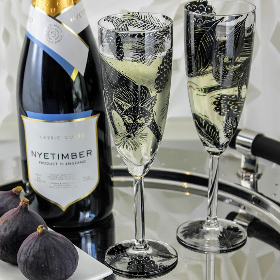 woodcut woodland scene two champagne flutes with foxes an Nyetimber sparkling wine
