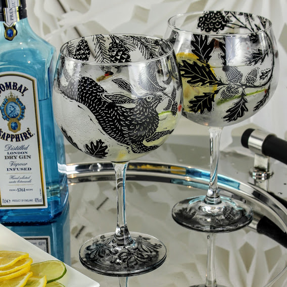 Bombay sapphire london dry gin pair of gin and tonic glasses with dancing hares in a oak forest